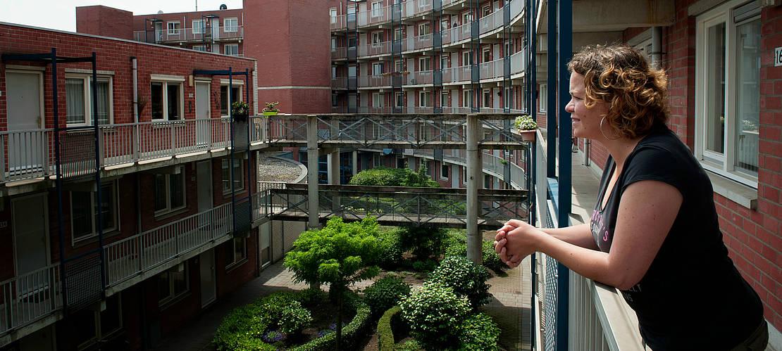 bewoonster kijkt vanaf haar balkon over de binnentuin van het wooncomplex